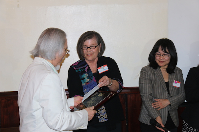 Prof. Tsuchida receiving recognition plaque